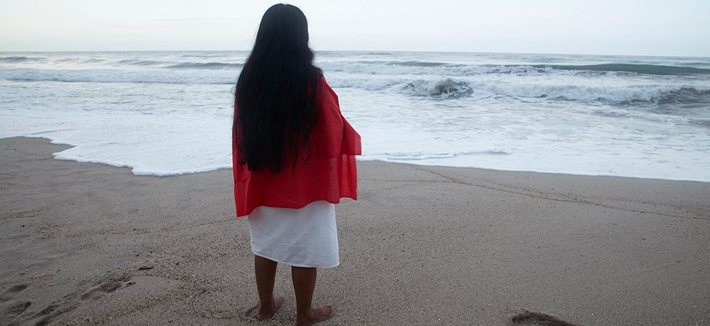 A woman stands on a sandy beach with her back to the camera; she is wearing a white dress with a bright red shawl draped over her shoulders.