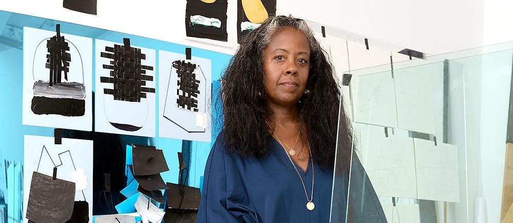 The artist, Torkwase Dyson, a woman in a blue shirt with long black hair, standing in her art studio in front of her artwork.