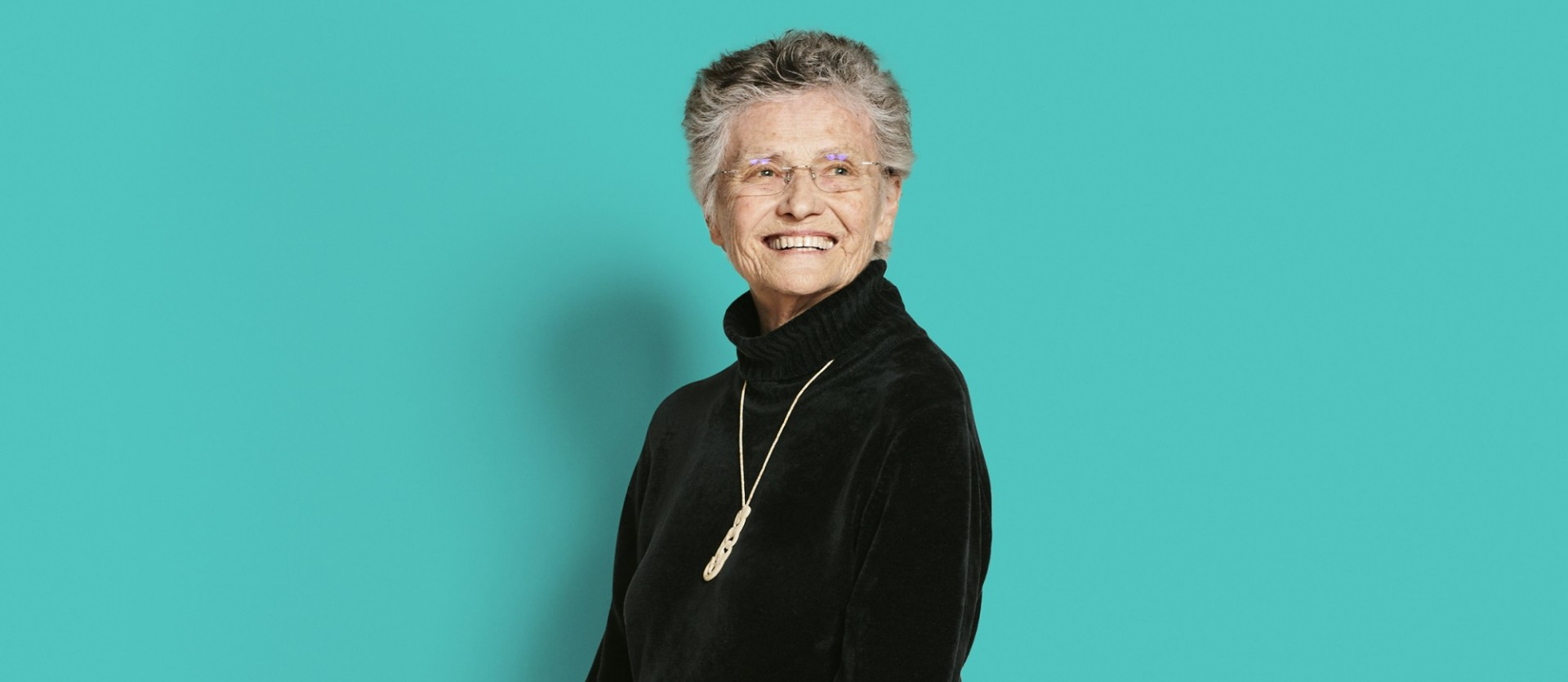 Musician Annea Lockwood: Woman with gray hair and glasses with black shirt with silver necklace in front of a turquoise-colored background.
