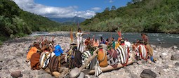 About a dozen people dressed in colorful tribal costumes sitting on a rocks and logs near a river with mountains in the background.