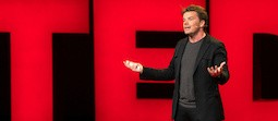 Architect Bjarke Ingels, brown hair, dressed in dark colors, speaking on a stage with red neon letters, spelling TED, behind him.