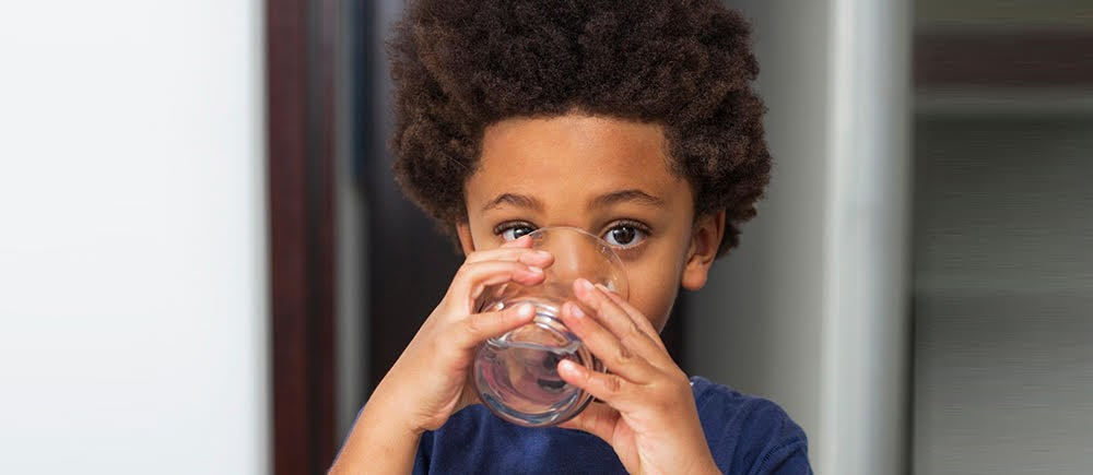 A young boy drinking from a glass of water.