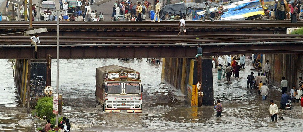 A bus being driven through a heavily flooded city.