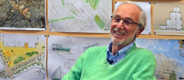 Architect Renzo Piano: Man with gray hair and beard with glasses wearing a lime green sweater and blue collared shirt sitting in front of maps and architectural drawings.