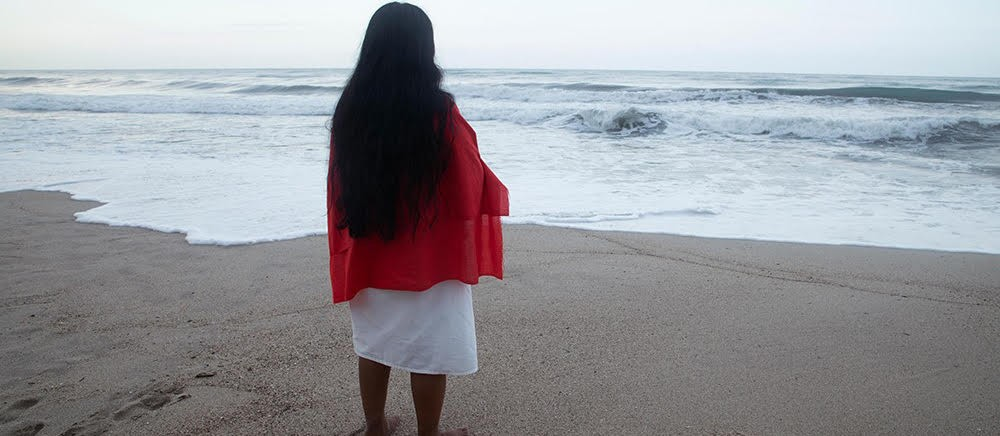 Woman with long black hair, wearing red shawl and white dress, with her back to camera looking out to the sea.