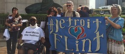 "Group of people holding a blue banner that reads ""Detroit Flint."""