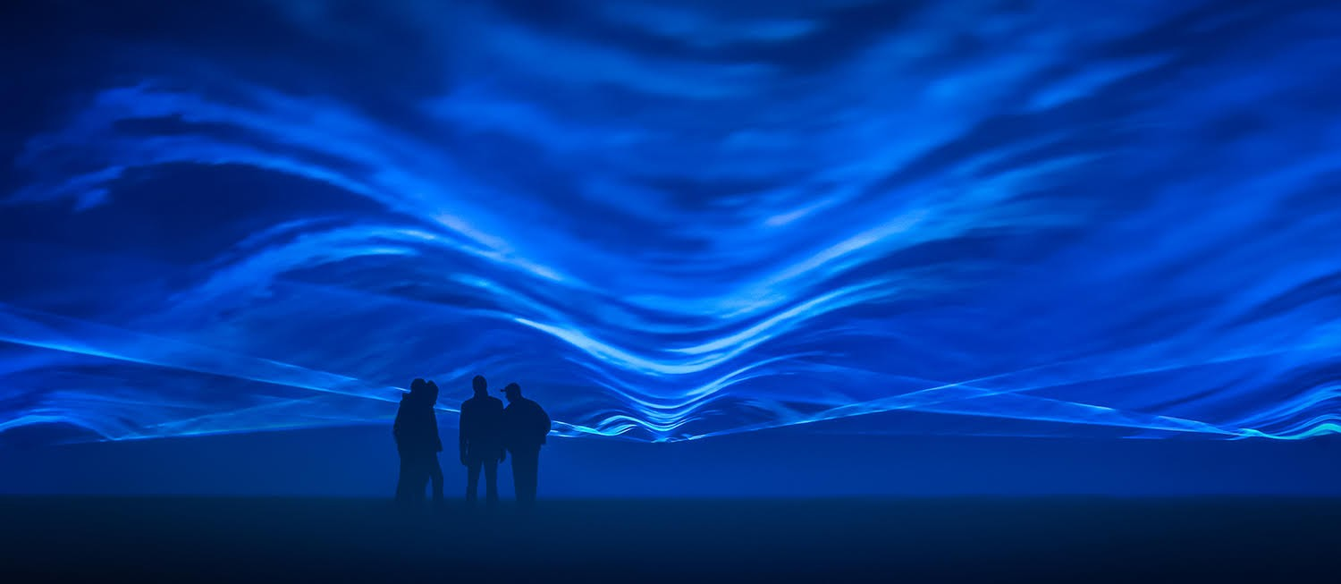 Blue waves of light with shadows of four people standing in the foreground.
