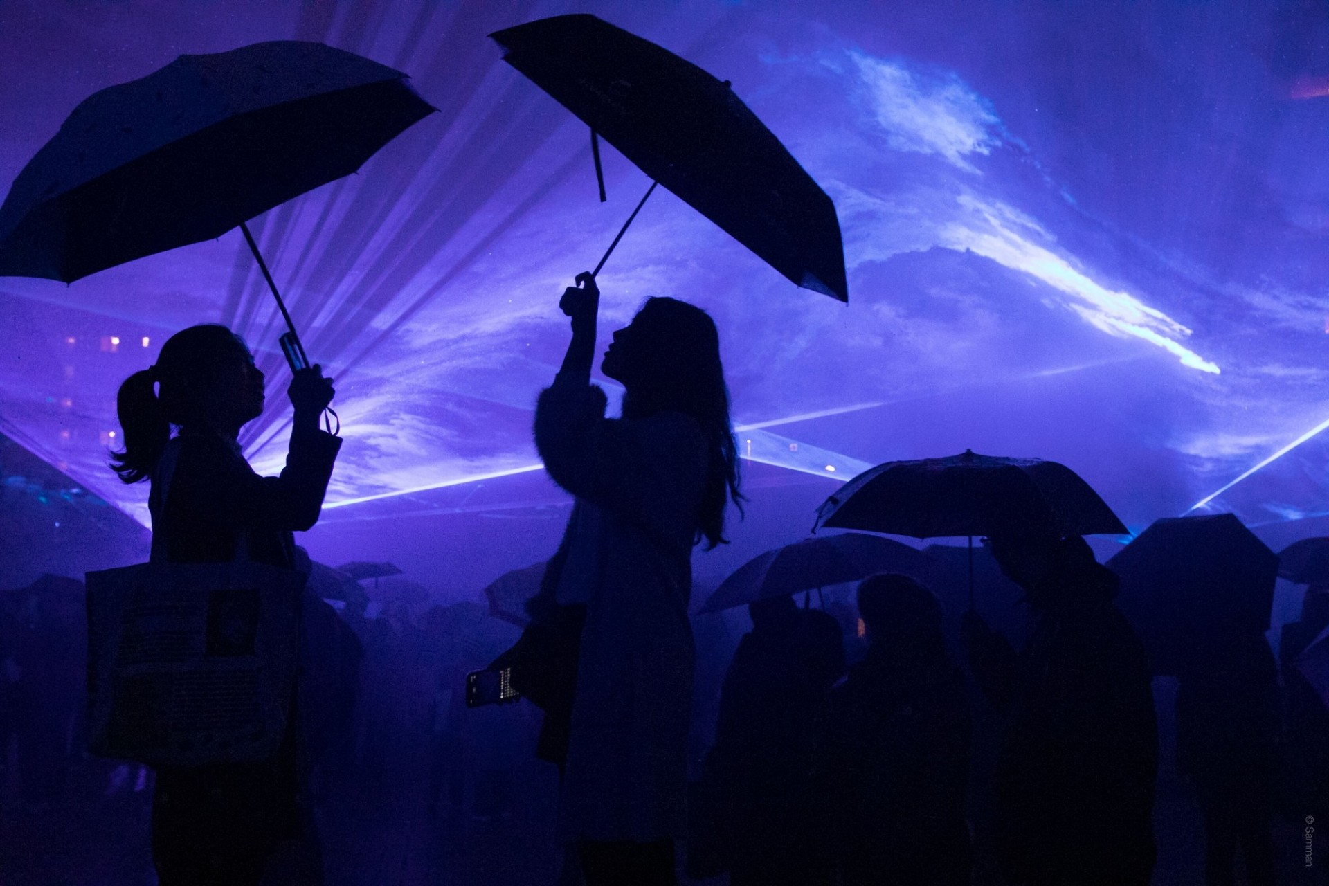 People in silhouette with umbrellas against a blue background of light