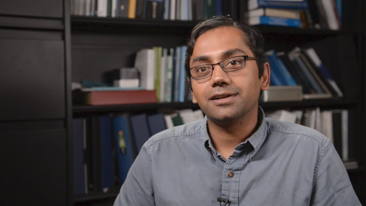 Kartik Chandran, man with glasses talking into the camera, with a shelf of books behind him.